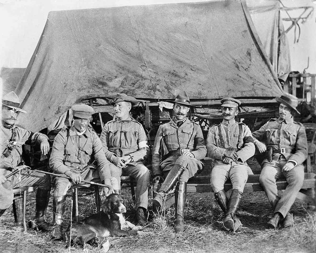 six men in uniform sitting down in front of tent