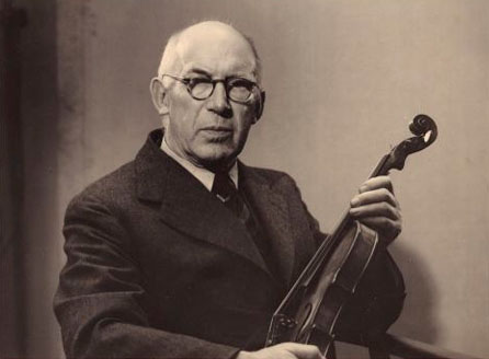 Sepia photo of a man seated, holding a stringed instrument.