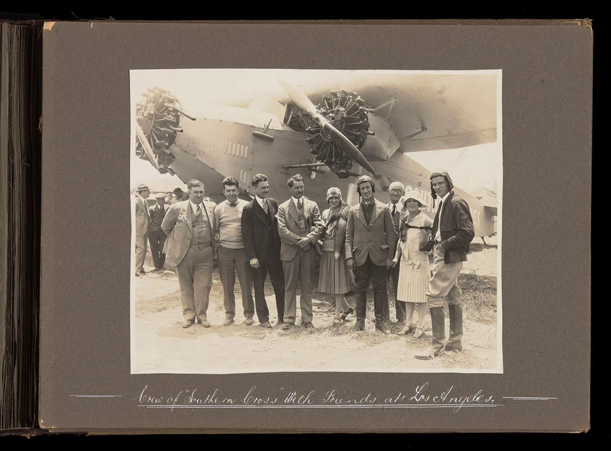 Nine people standing in a line in front of 'Southern Cross'. - click to view larger image