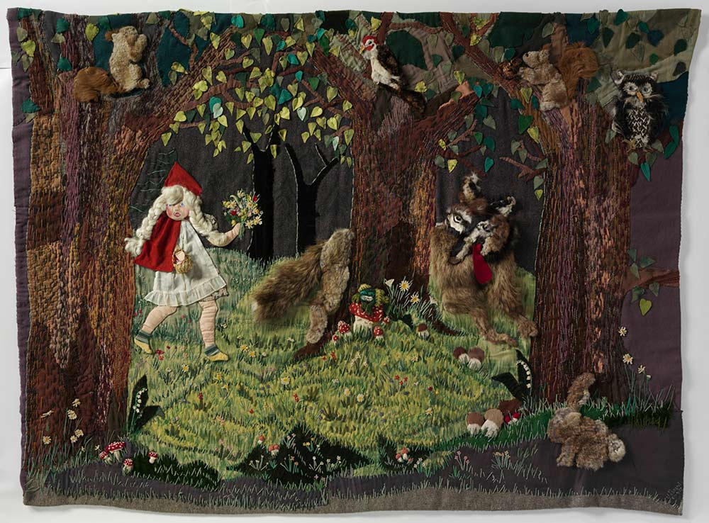 Wall hanging depicting Little Red Riding Hood walking through a forest. A wolf appears from behind a tree, with his red tongue hanging out the side of his mouth. A variety of fabrics including felt and fur have been sewn onto a grey blanket to form the scene, which also shows an owl, a bird, a squirrel and a rabbit. Some of the elements are padded using a technique called stumping, and they have a three-dimensional appearance.