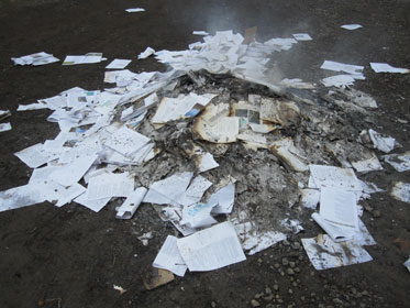 Colour photograph of a smoulder pile of papers on a dirt base.