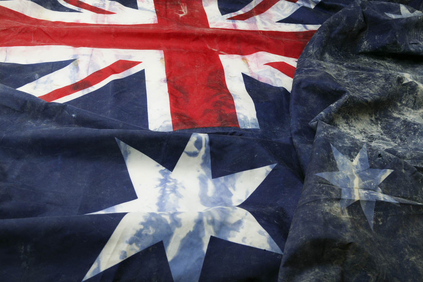 Top left section of an Australian flag with stains, tears and burns. The Union Jack is visible, along with the large seven-pointed star. The section bearing the Southern Cross is quite crumpled.