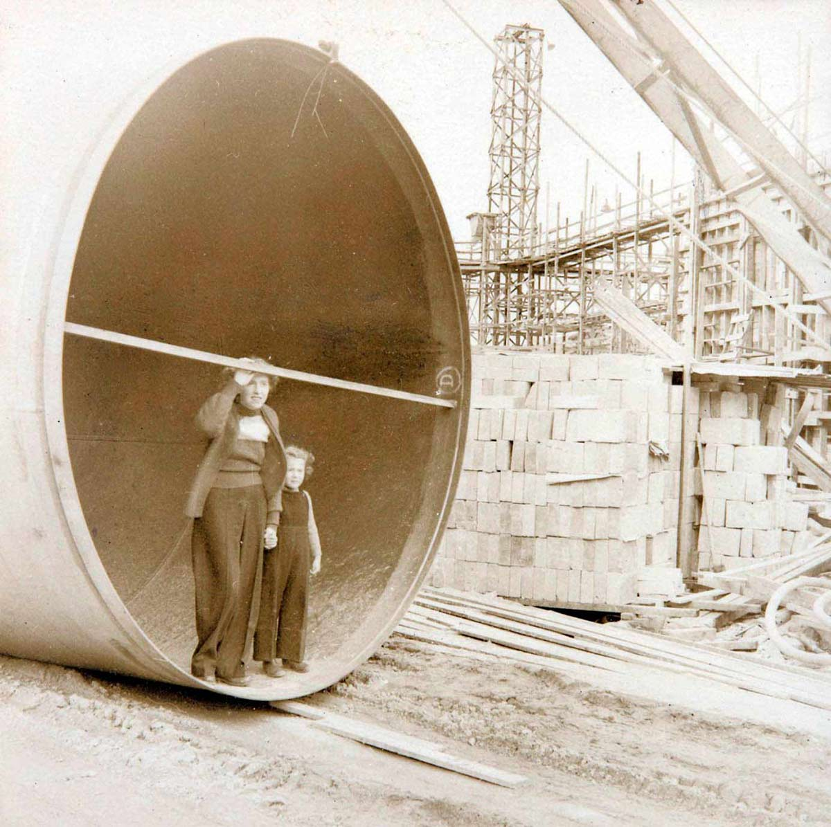Photograph of a woman and a young girl standing inside the open end of a very large pipe at a building site. - click to view larger image