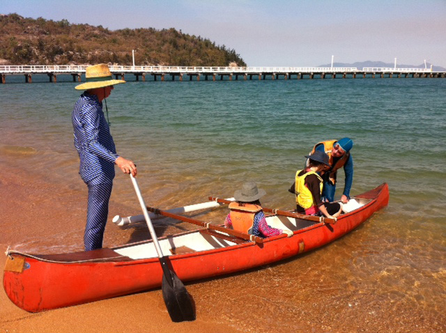 Canoe on the shore with four people. - click to view larger image
