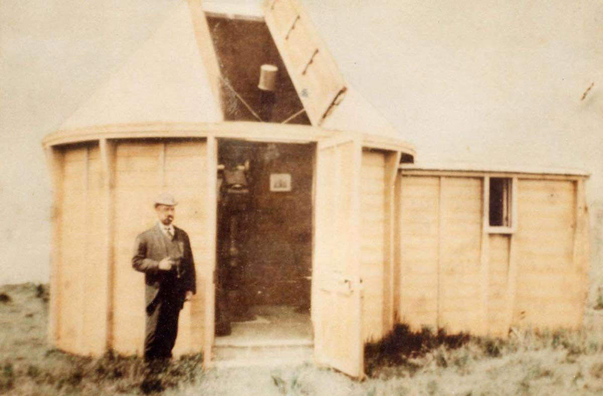 A man wearing a suit and hat stands beside a timber observatory building. The door and the roof of the circular structure are open, revealing a telescope inside.