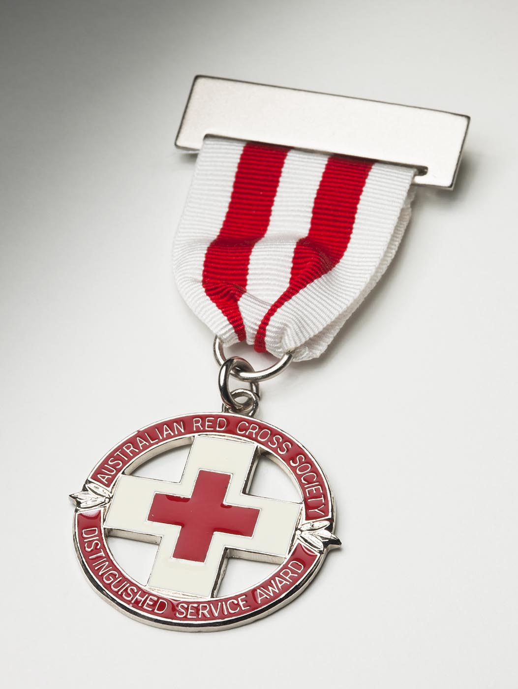 A Red Cross badge hanging from a silver bar and a ribbon with vertical white and red stripes. The circular award features a central red on cross on silver background, with the words 'AUSTRALIAN RED CROSS SOCIETY / DISTINGUISHED SERVICE AWARD' on an outer circle. - click to view larger image