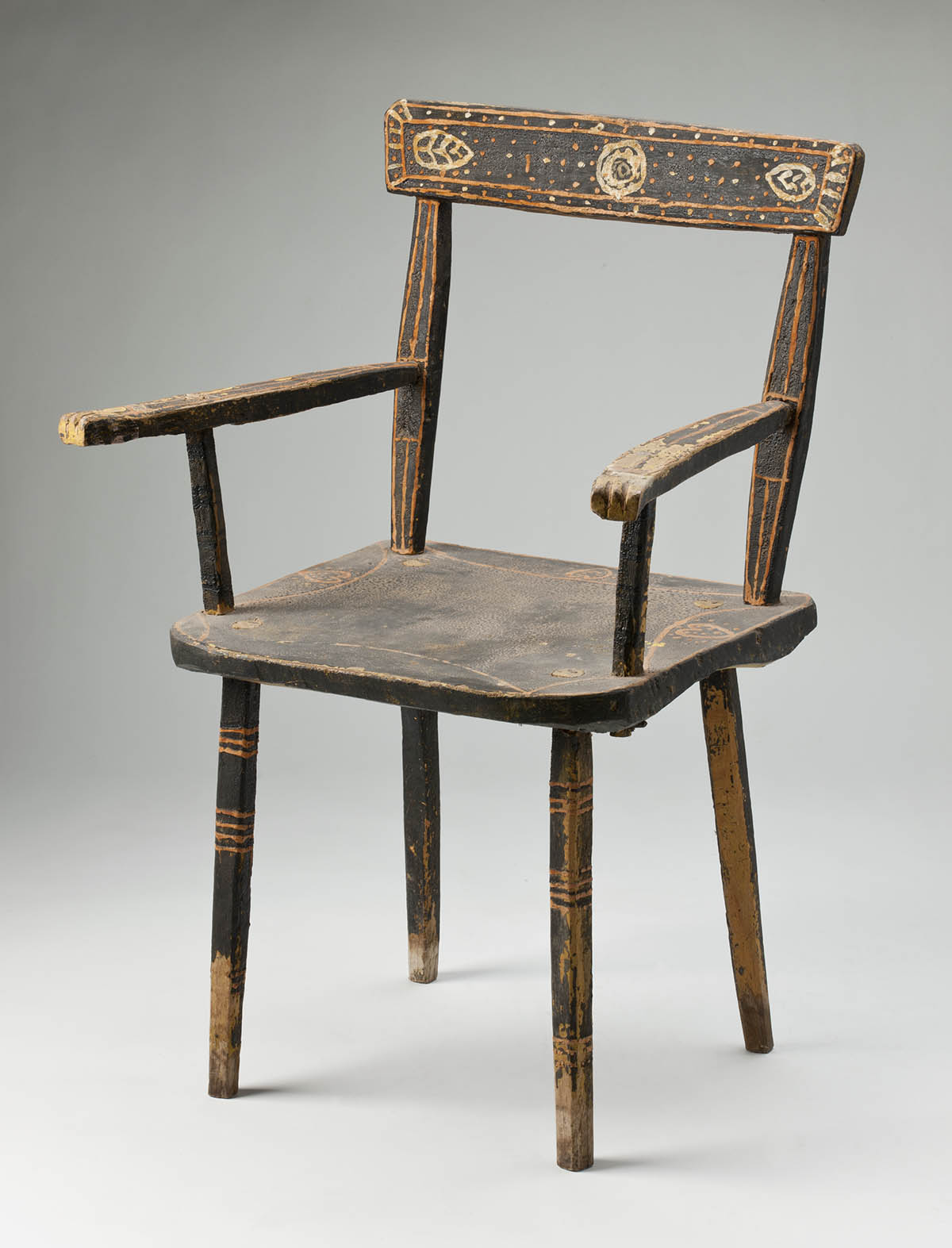 A wooden chair painted primarily in a dark brown, decorated in shades of orange and light brown on the arms, legs and back. - click to view larger image