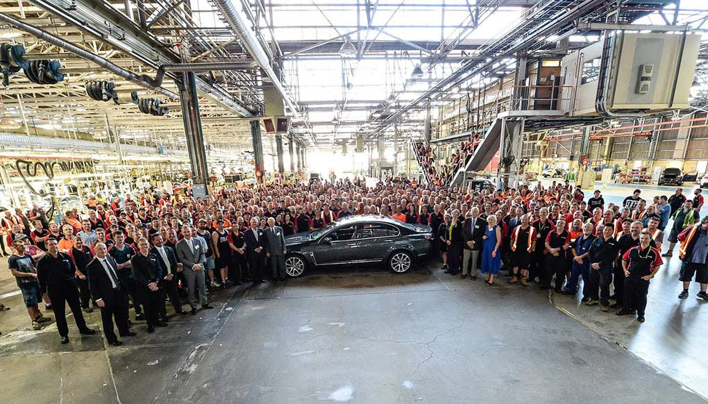A crowd of people gather around a car and pose for a photograph.