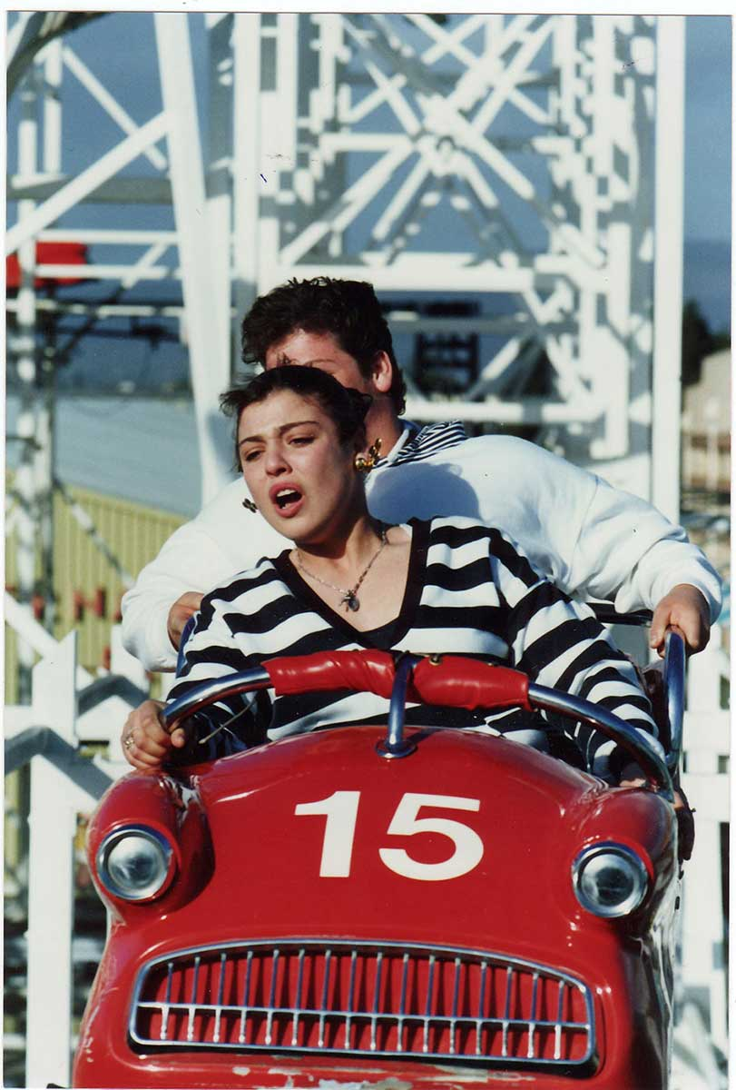A woman sits at the front of a red rollercoaster car, with another person partially visible in the seat behind. - click to view larger image