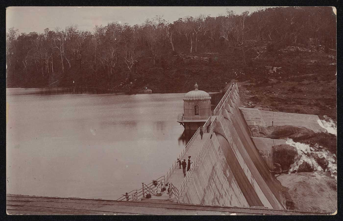 A sepia photo taken from above a concrete dam wall. Several people stand on the wall, looking at the water on one side, and the spillway on the other. - click to view larger image