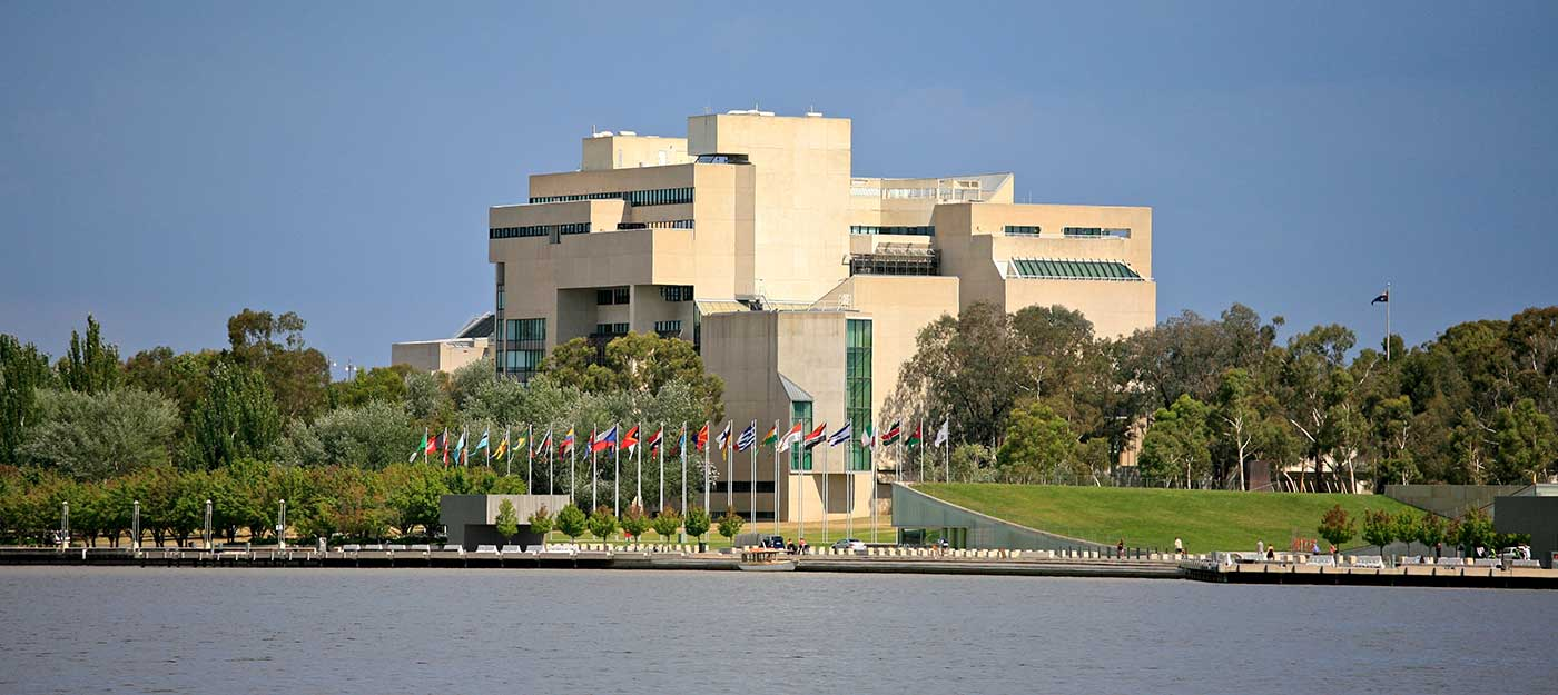Colour photograph showing an exterior view of the High Court, taken from across the lake. A row of flags flies on the lake shore, outside the court building. - click to view larger image