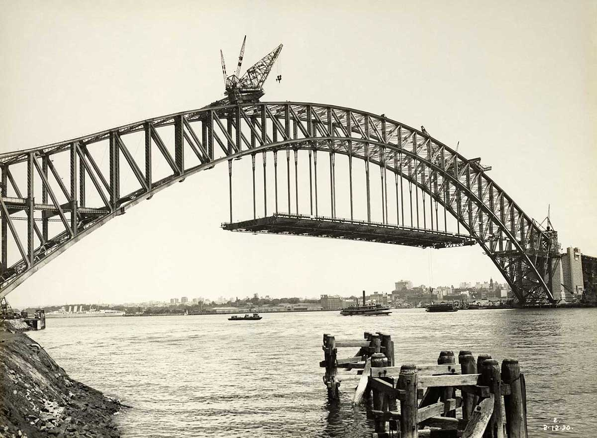Black and white photograph of the partially constructed Sydney Harbour Bridge, with part of the road deck hanging below the main arch. - click to view larger image