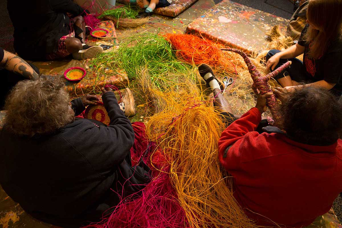 Women sitting and weaving objects. - click to view larger image