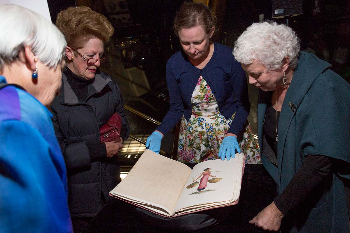 Four women looking at a book.
