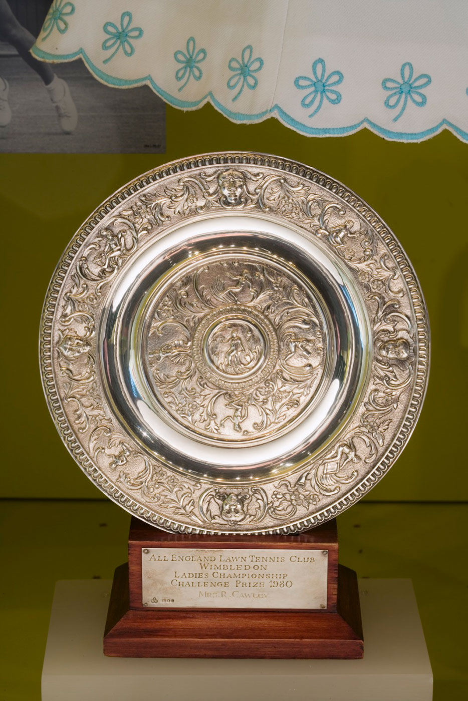 Ornate silver disc presented on a wooden stand. Inscribed text on the stand reads: 'All England Lawn Tennis Club Wimbledon Ladies Championship Challenge Prize 1980 awarded to Mrs R Cawley'. - click to view larger image