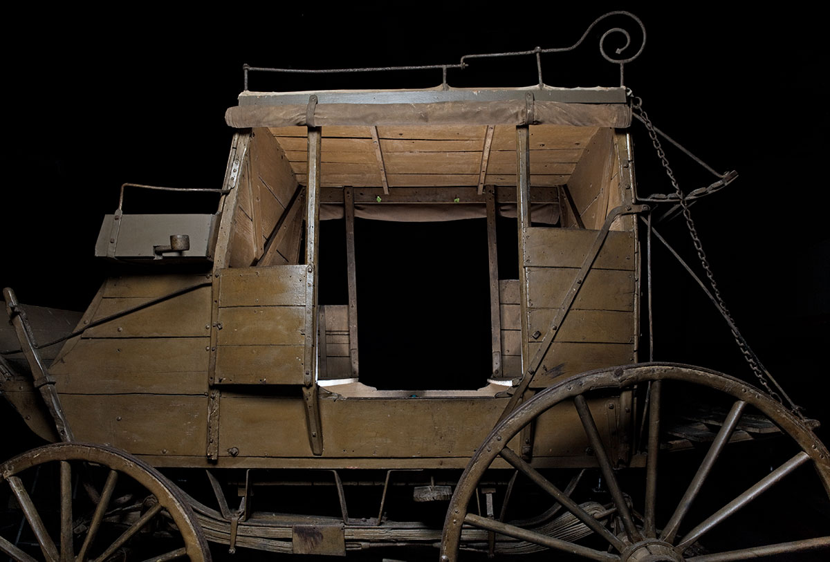 A horse-drawn, four-wheeled, eight-passenger 'stage' coach made from wood reinforced with iron strips and brackets - click to view larger image