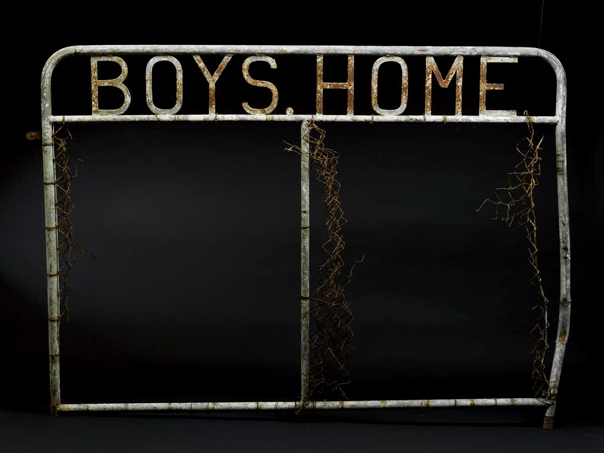 A metal gate with welded metal letters at the top which reads 'BOYS HOME'. - click to view larger image