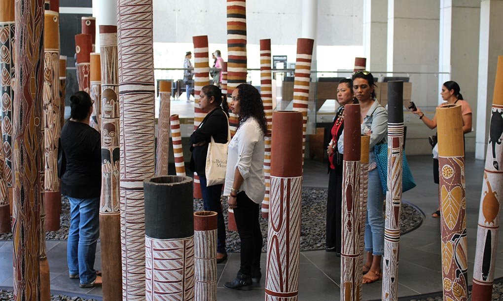 A group of women stand in between a number of hollow wooden logs which stand upright and are painted with Australian Indigenous artwork. - click to view larger image