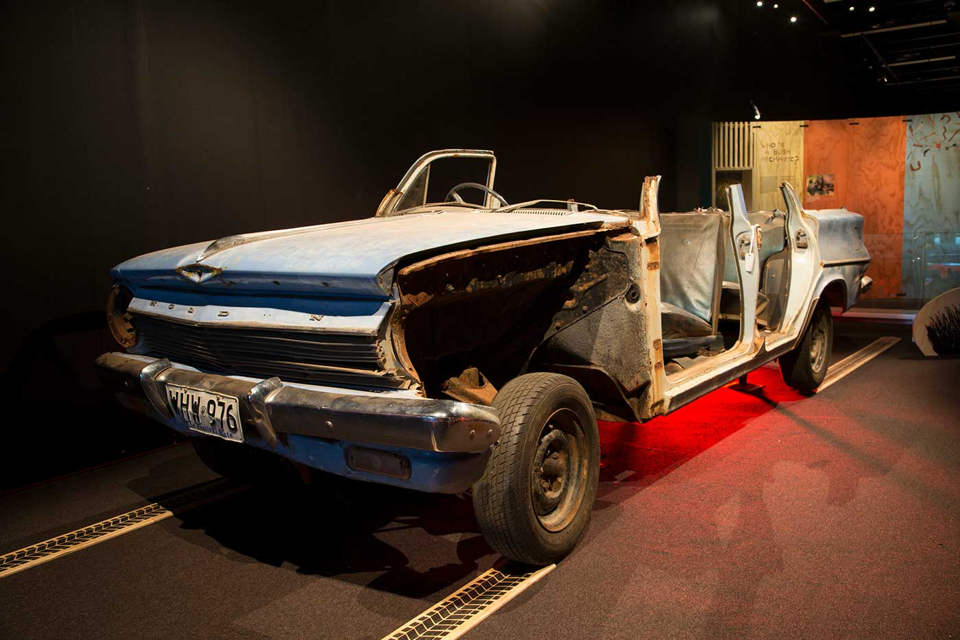 Blue Holden car missing its roof and most passenger side panels. - click to view larger image