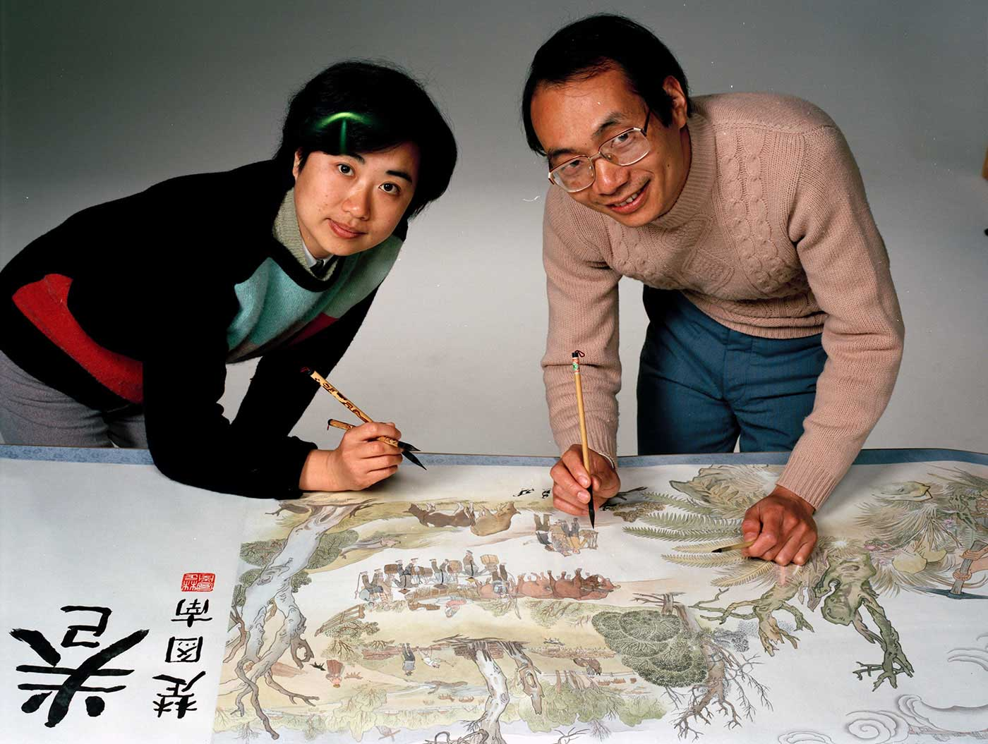 Artists Mo Xiangyi (right) and Wang Jingwen (left) add some finishing touches to the scroll.