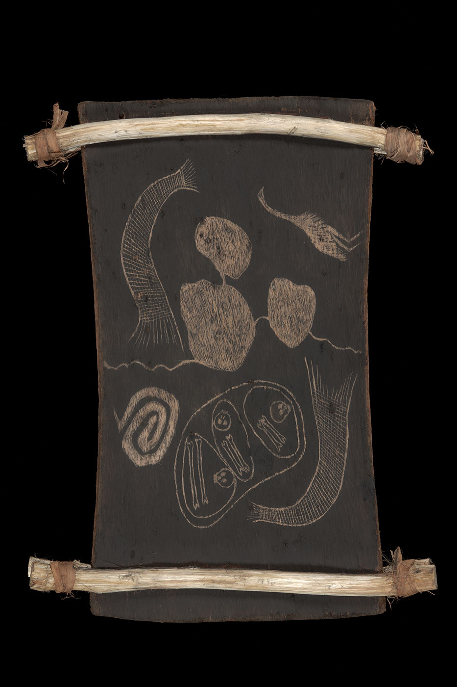 A bark etching supported between two pieces of split wooden restraints. The etching features three skulls and six bones, an emu, two fishnets, a coil shaped pattern to the left lower side and three irregular round shapes represented as lakes. - click to view larger image