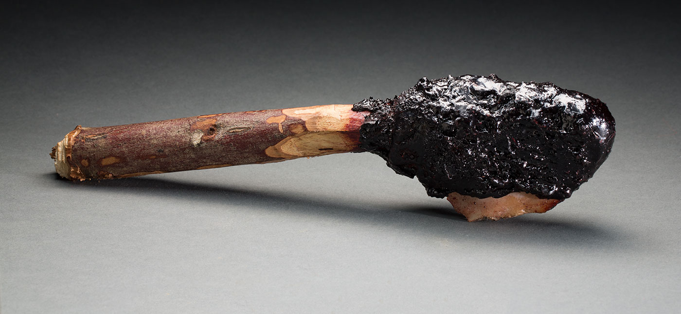 A stone axe made of a wooden stick attached to a stone and resin at the top end of it.  - click to view larger image