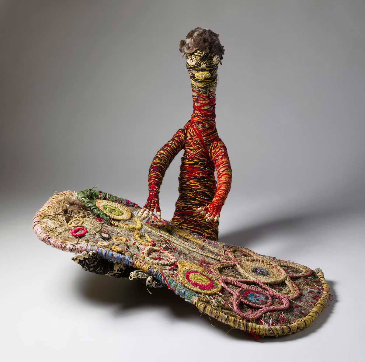 A sculpture depicting a person working on a painting. The sculpture is made of woven grass, plant material dyed in different colours and strands of wool. - click to view larger image