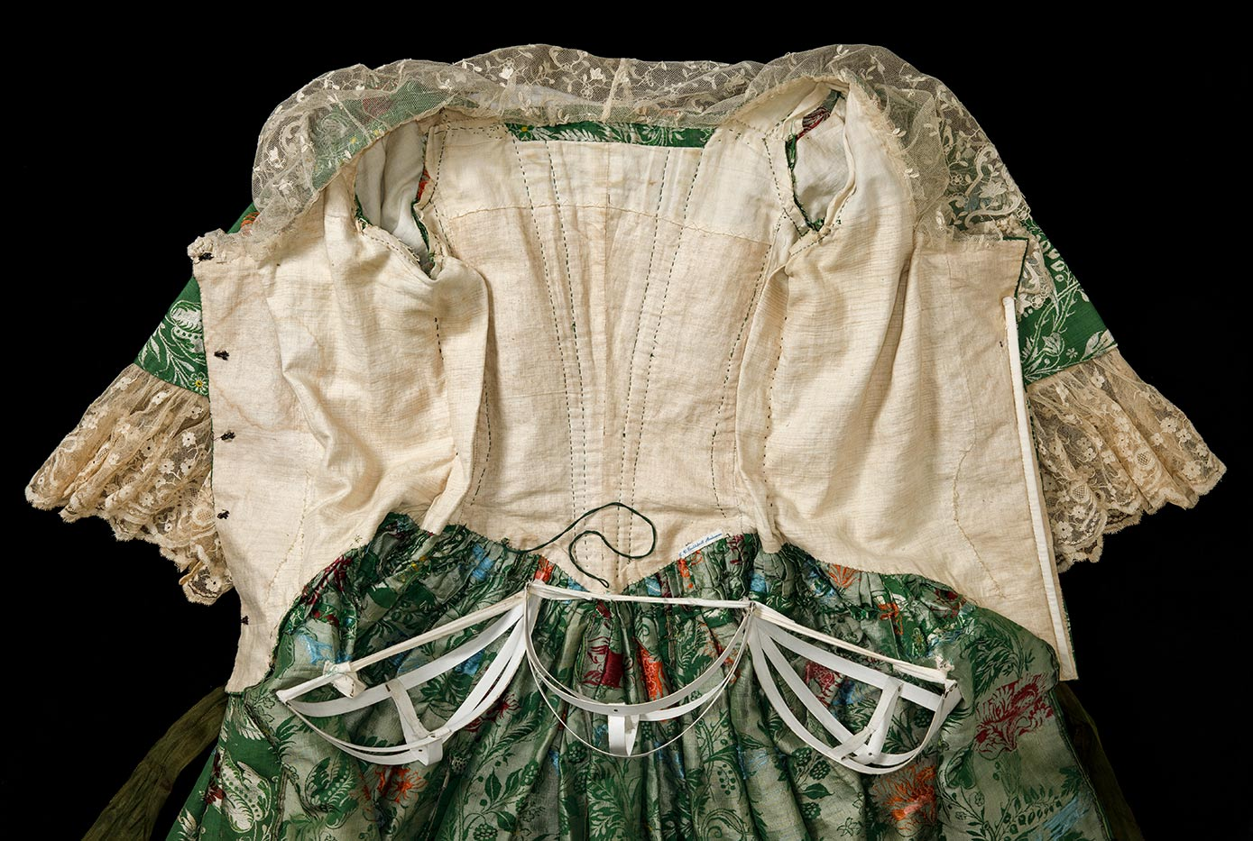 Green and floral brocade open-front robe features lace trim on sleeves and collar, and three small fabric-covered metal panniers. - click to view larger image