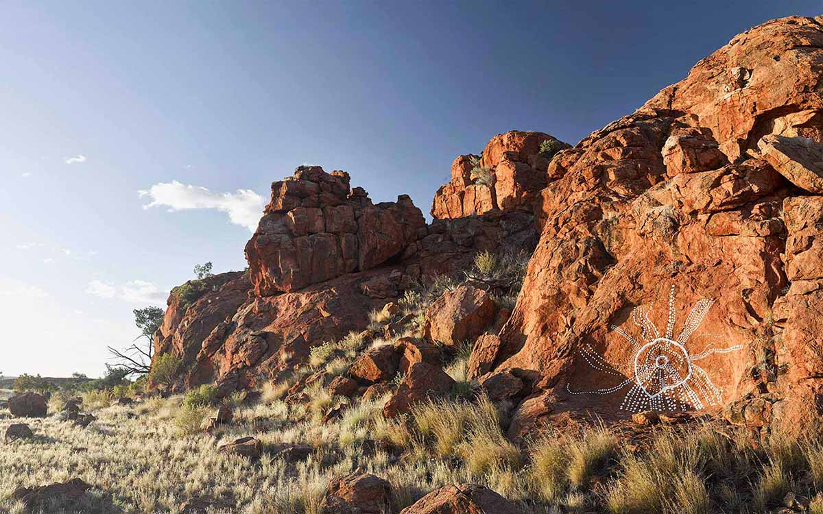 Landscape photography showing red rocks beside a grassy plain. Part of the largest rock in the right foreground has been painted with white dots extending from a central white circle. - click to view larger image