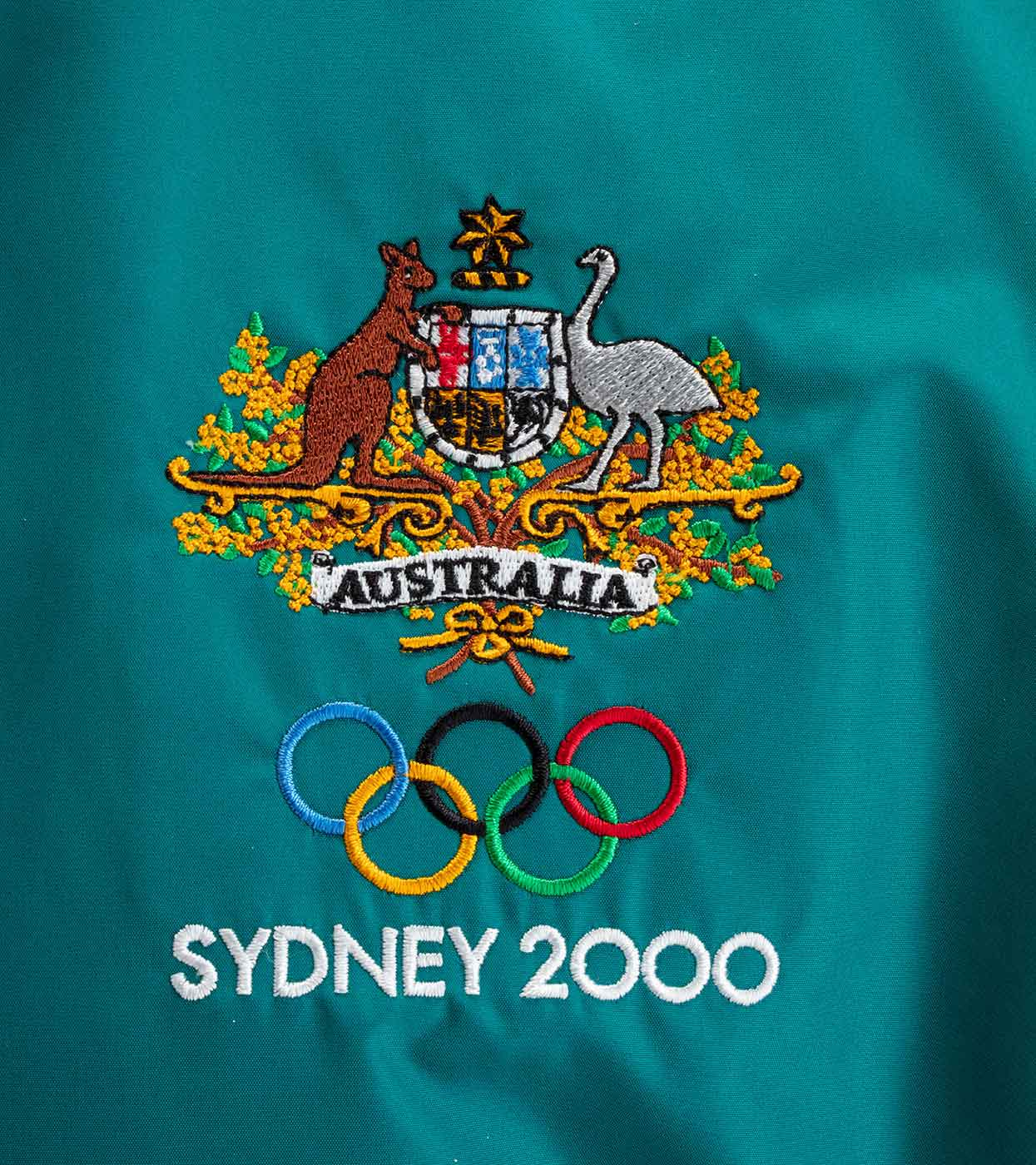 Close up of a tracksuit top with the Australian coat of arms and 'Sydney 2000' embroidered on it. - click to view larger image