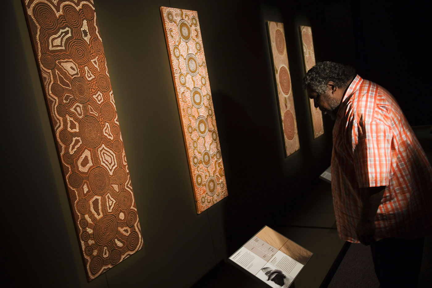 Visitor reading label in front of Aboriginal dot paintings. - click to view larger image