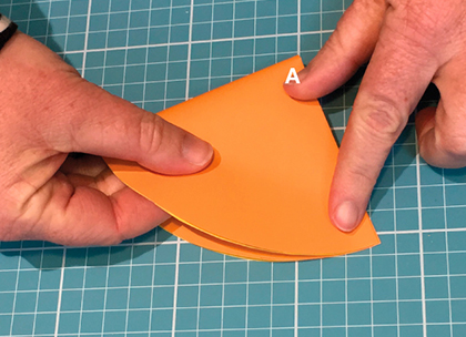 A large orange star cut out from orange paper. Two fingers point to two points on each side of the star.