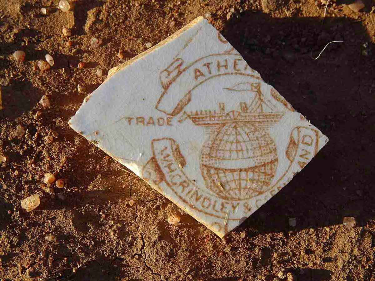Piece of broken ceramic plate showing partial trademark of its English manufacturer