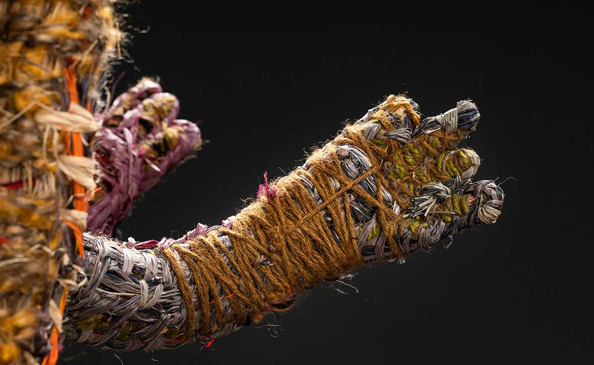 A detail image of human like hands. The sculpture is made of various plant-based and synthetic materials. - click to view larger image