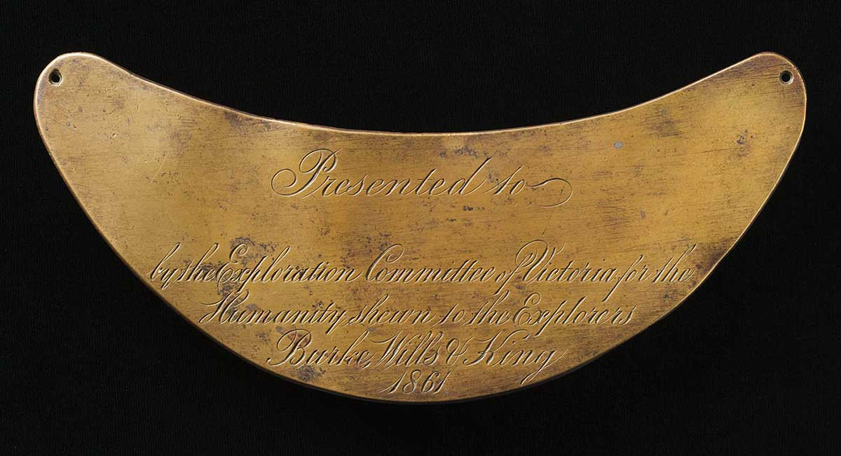Golden crescent-shaped metallic plate inscribed with th words 'Presented to (blank) by the Exploration Committee Victoria for the Humanity shewn to the Explorers Burke, Wills & King 1861'.