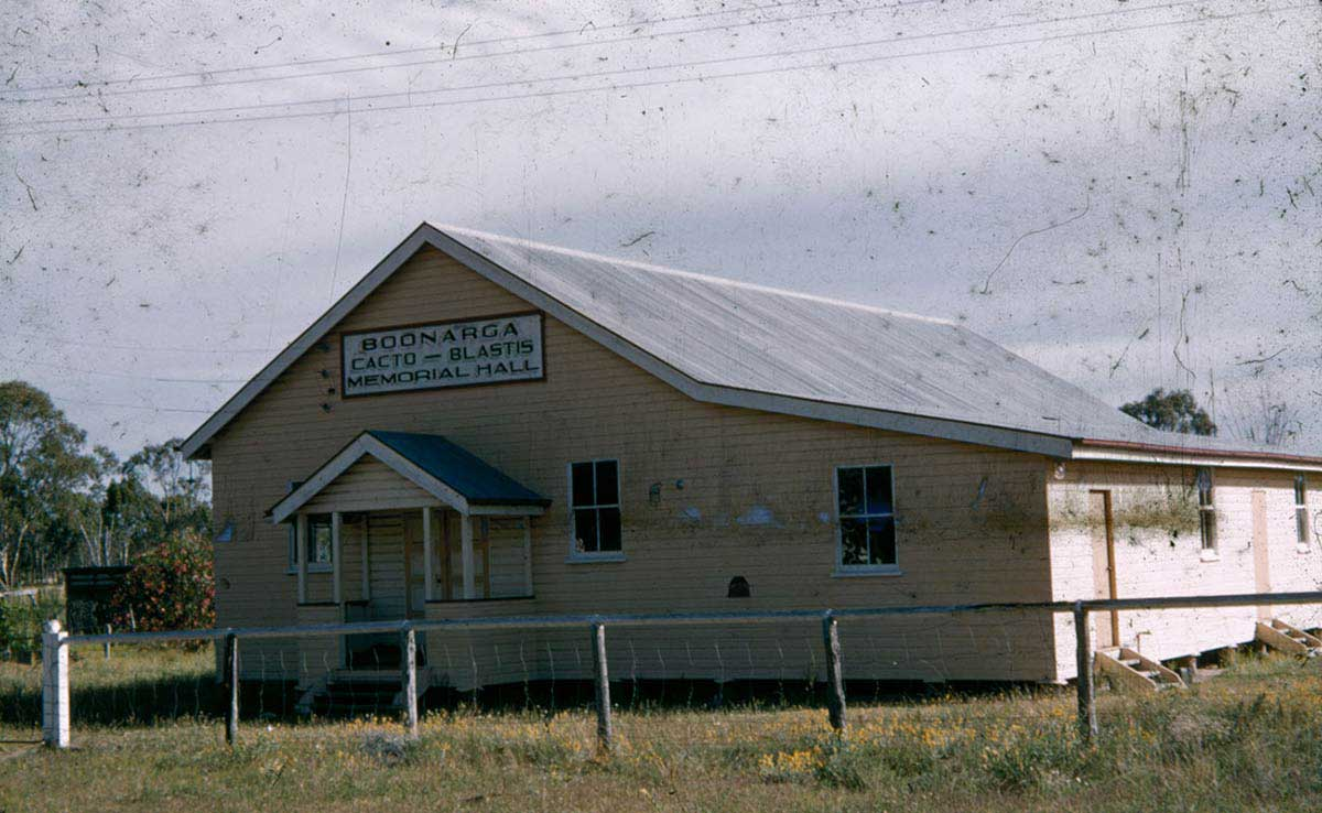 A single-storey weatherboard building, painted pale yellow, with a corrugated iron roof. A painted sign above the front entry says: 'Boonargo Cacto-Blastis Memorial Hall'. - click to view larger image
