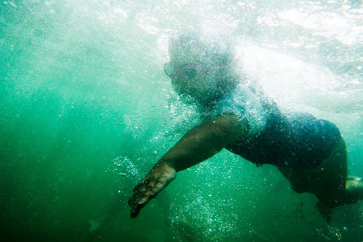 An underwater photograph of a person wearing goggles and swimming. - click to view larger image