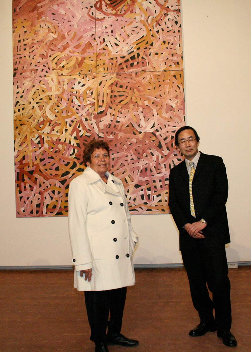 A woman and a man in formal wear standing in front of a large painting. - click to view larger image