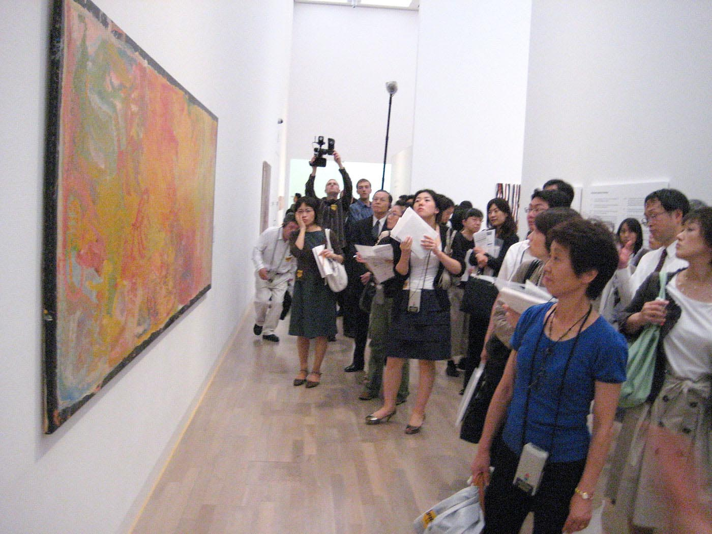 Media standing in front of a large painting. - click to view larger image
