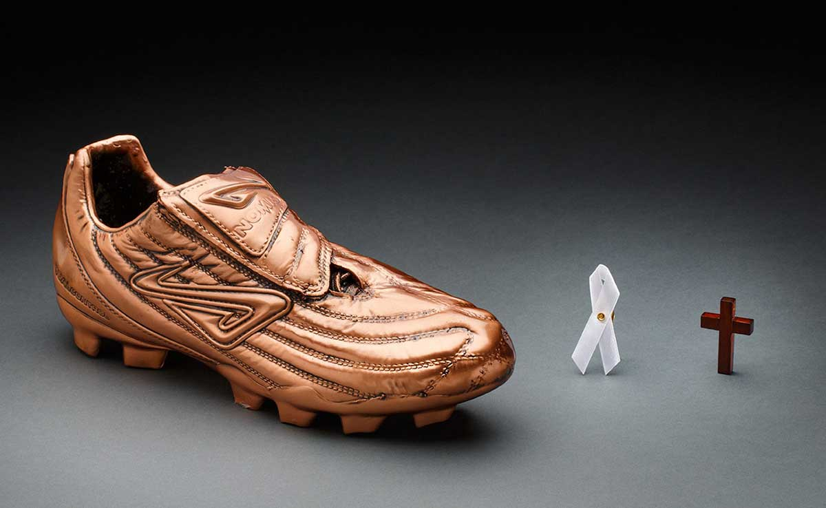 Bronze-coloured replica football boot, small white ribbon badge and small wooden cross