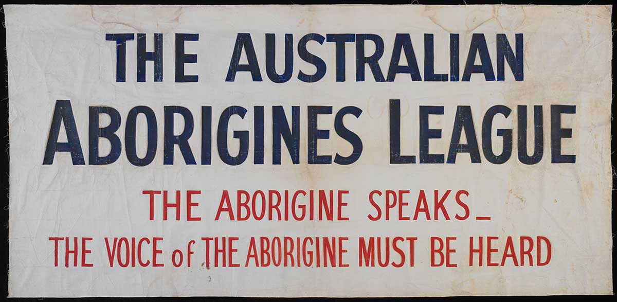 A rectangular calico banner featuring an inscription in blue and red paint which reads 'THE AUSTRALIAN ABORIGINES LEAGUE, THE ABORIGINE SPEAKS_THE VOICE of THE ABORIGINE MUST BE HEARD'. - click to view larger image