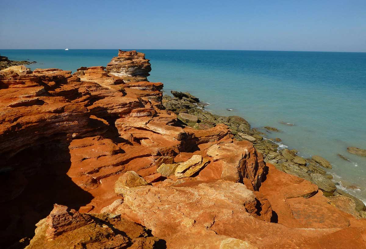 View of ochre cliffs overlooking a calm sea.