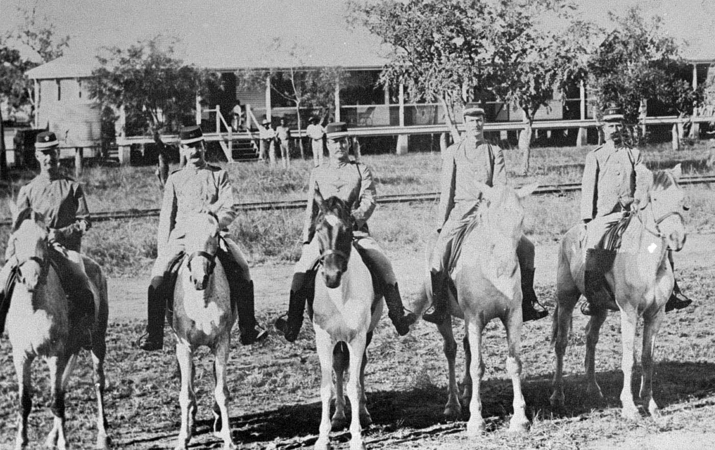 A group of five mounted police with a police quarters in the background.