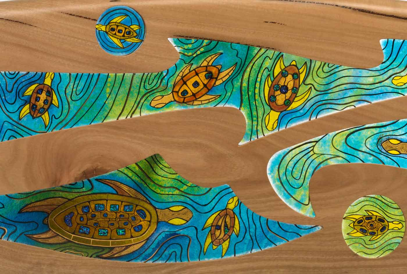 Detail of a sculpture made of carved wood in the shape of a surfboard inset with infused coloured glass, featuring turtle motifs swimming through water. - click to view larger image
