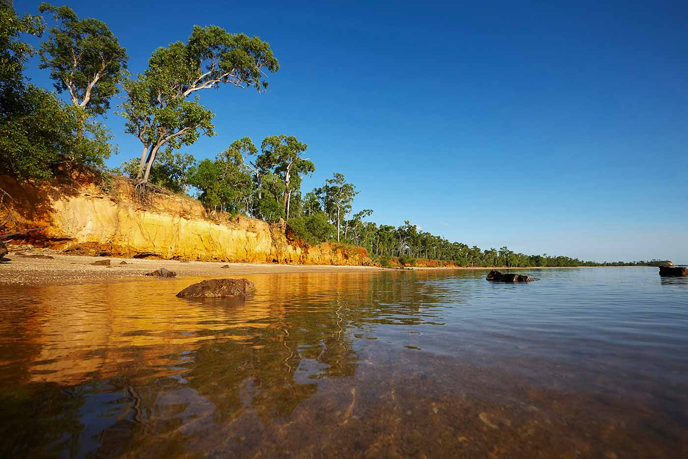 View of yellow ochre sheer rock formations and trees running alongside a river with clear and calm waters.