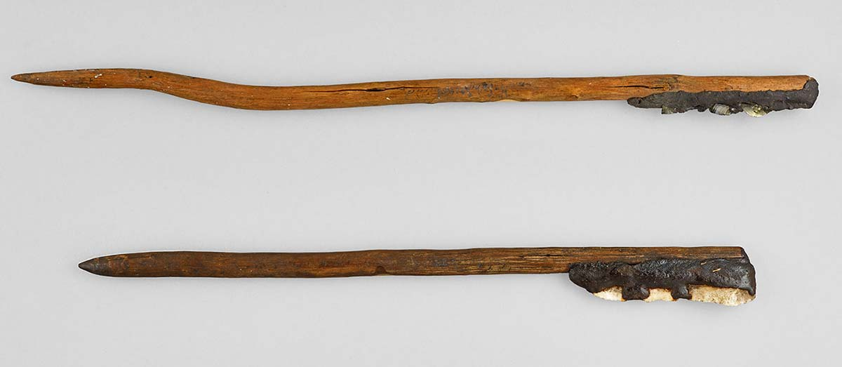 Long wooden handled knives, with blades of stone and glass, adhered with resin.