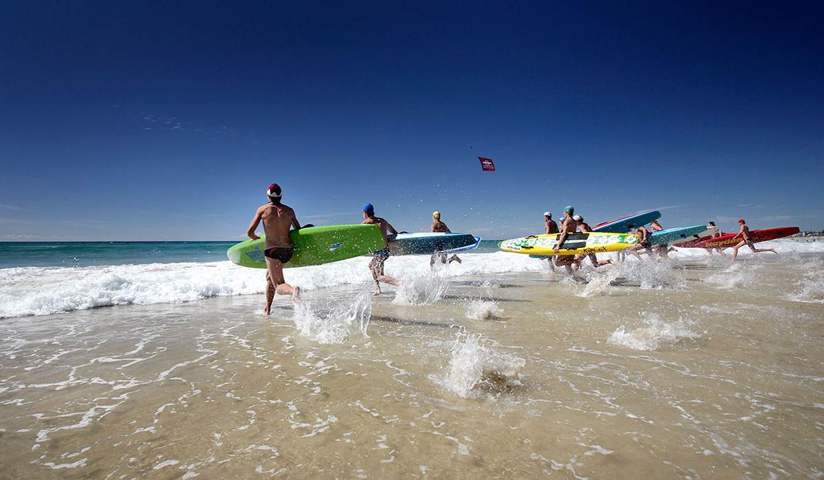 Lifesavers running into the surf with their boards at the Australian Surf Life Saving Championships, Kurrawa, Queensland, 2006.