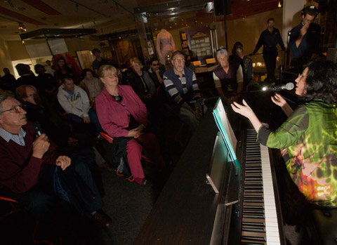 A colour photograph of Elena Kats-Chernin sitting at an electric piano while she talks to a group of people standing in a rough semi-circle around the piano. They are located in a museum exhibition and display cases can be seen in the background, despite the low level of the lighting.