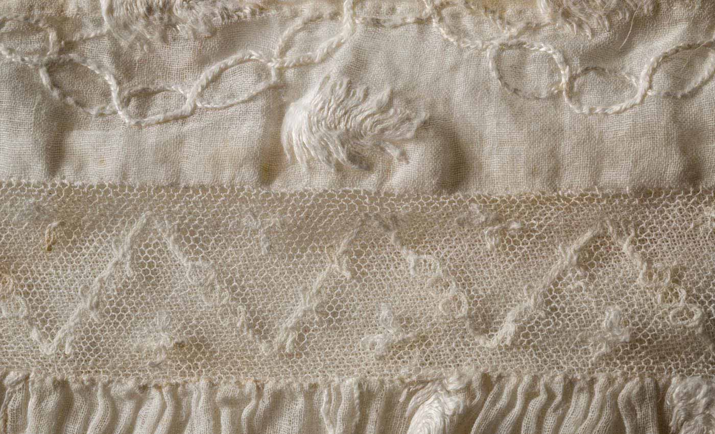 Detail of machine-embroidered net inserted into the bodice of the dress during a later alteration. - click to view larger image
