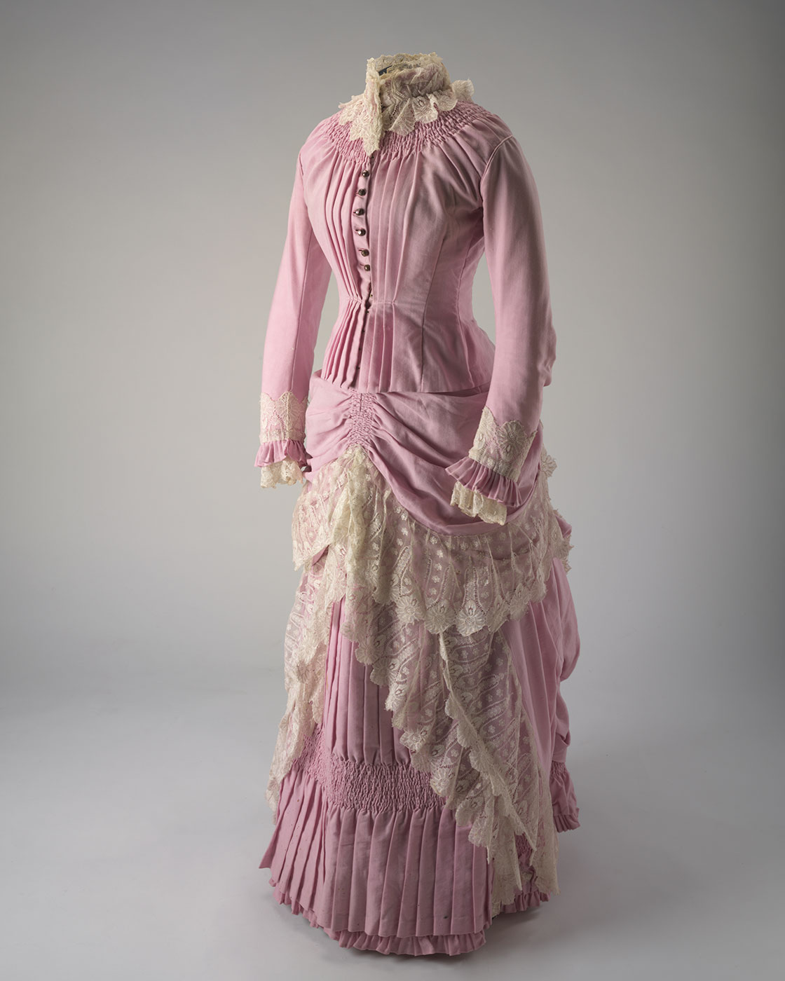 Front view of a two piece pink full length wool dress (bodice and skirt) with cream lace trimming. - click to view larger image